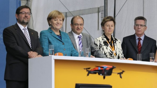 German Chancellor and head of CDU party Merkel and Defence Minister de Maiziere look at a quadrocopter before it crashes into the stage during CDU election campaign event in Dresden